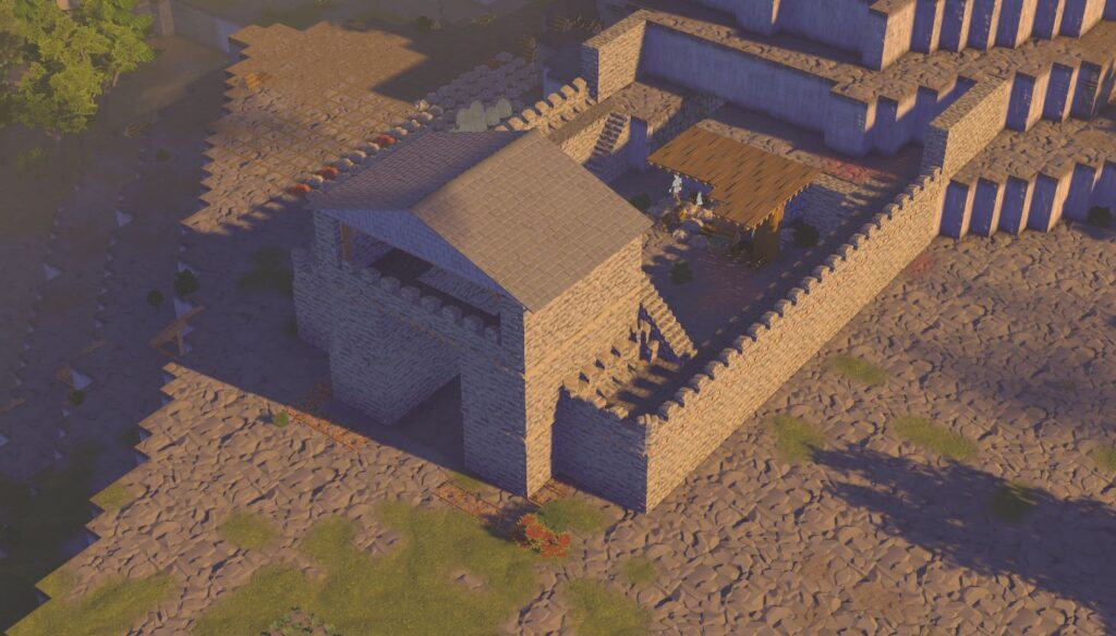 A large stone castle wall in front of a base in a mountain in Going Medieval
